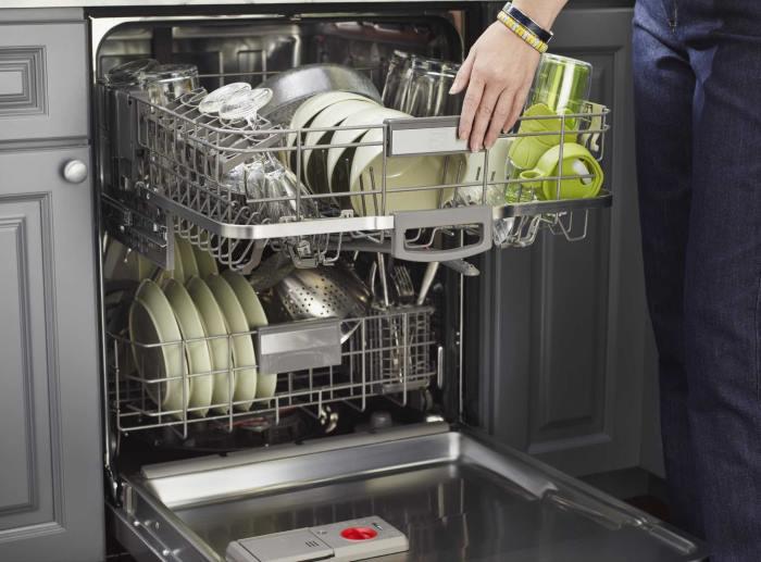 Полная загрузка посуды в полноразмерную двухярусную посудомоечную машину на кухне