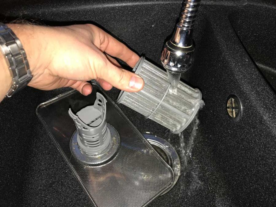 Тщательная промывка сливного фильтра посудомоечной машины Бош под струей воды