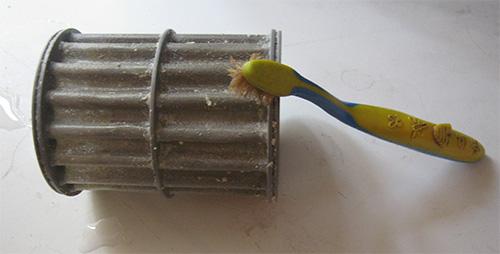 Эффективно очистить сливной фильтр посудомойки от остатков пищи можно с помощью зубной щетки