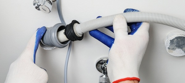 Мастер выполняет работу по замене сливного шланга для бытовой посудомоечной машины