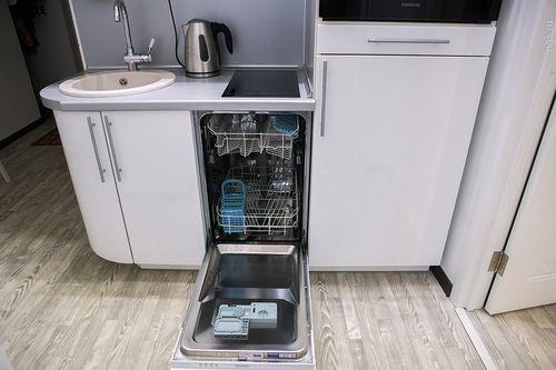 Пример размещения узкой посудомоечной машины на компактной кухне под варочной панелью