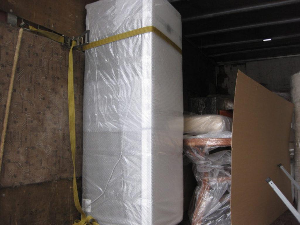 При перевозке холодильника в большом грузовике желательно его дополнительно закрепить к борту